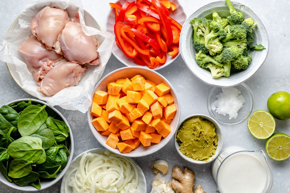 Thai green chicken curry ingredients arranged on a light blue surface - chicken thighs, bell pepper, broccoli, sweet potato, coconut oil, limes, coconut milk, green curry paste, ginger, garlic, onions & spinach.
