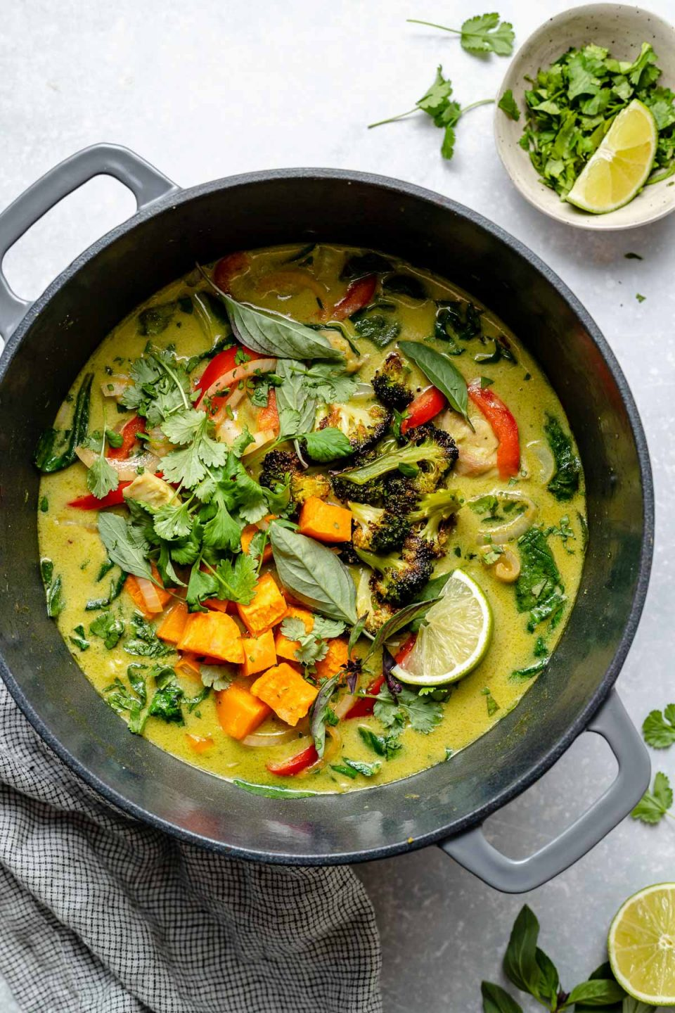 Thai green chicken curry in a large Dutch oven atop a light blue surface. The curry is topped with fresh cilantro & Thai basil. The Dutch oven sits atop a light blue surface next to a checkered blue & white linen napkin, limes & a small bowl of chopped green herbs.