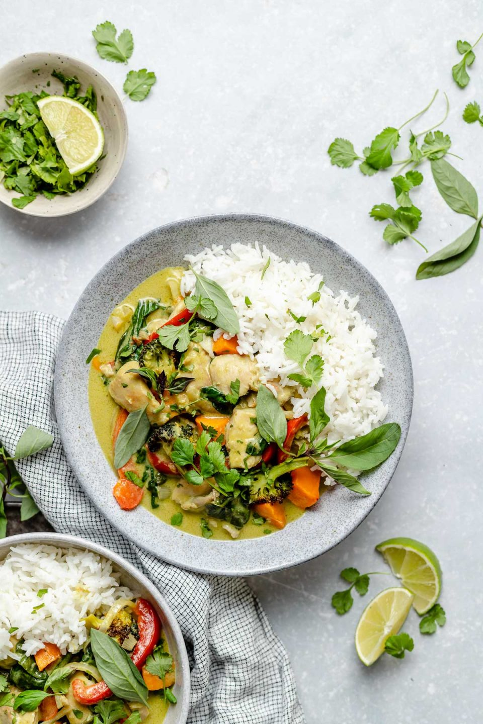 Thai green curry chicken in bowls with fluffy white rice, topped with fresh cilantro & Thai basil. The bowls sit atop a light blue surface, next to lime wedges, fresh herbs, & a checkered blue & white linen napkin.