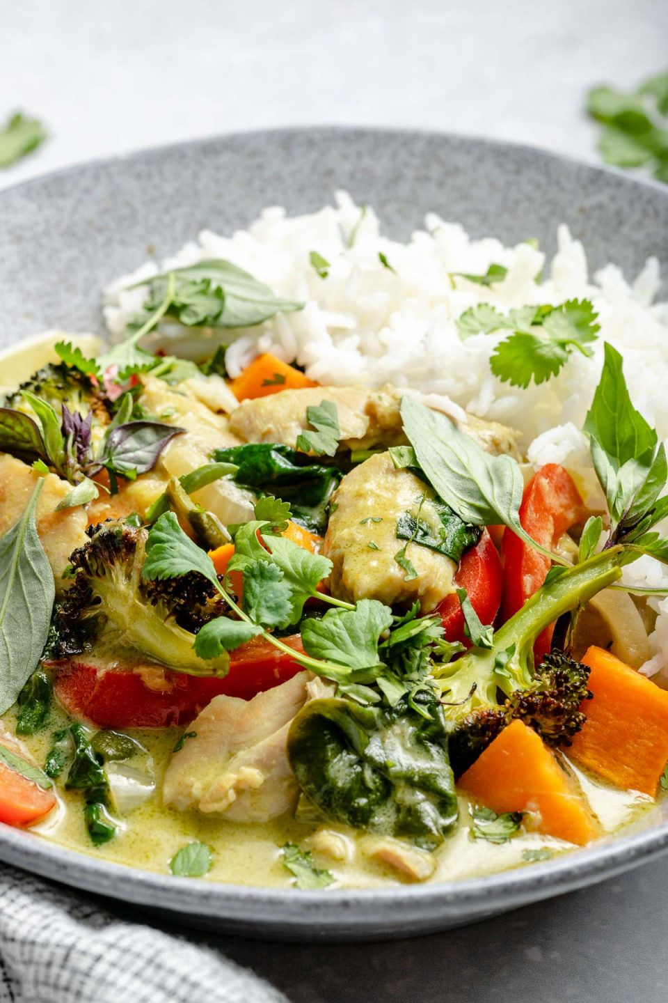 Side angle of Thai green curry in a serving bowl atop a light blue surface next to a checkered blue & white linen napkin. Cilantro leaves are in the background, behind the bowl.