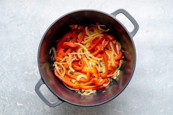 How to make Thai green curry, Step 4: Onions & bell pepper soften in a large Dutch oven. The Dutch oven sits atop a light blue surface.
