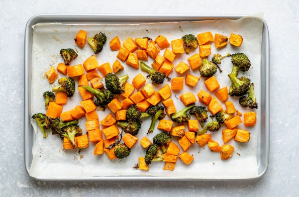 How to make Thai green curry, Step 3: Sweet potatoes & broccoli on a small baking sheet after roasting. The baking sheet sits atop a light blue surface.