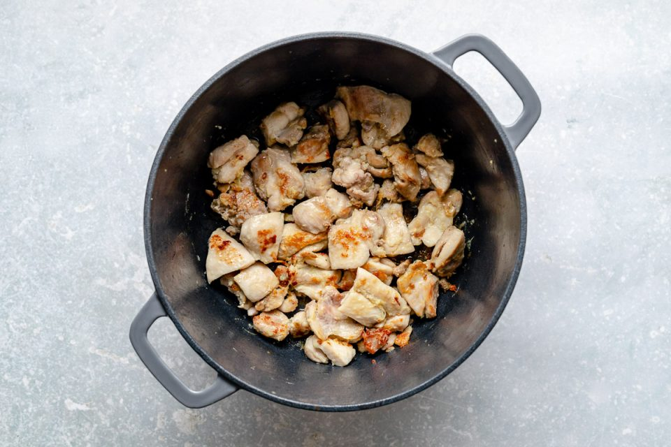 How to make Thai green curry, Step 5: Gingery chicken sears in a large Dutch oven. The Dutch oven sits atop a light blue surface.