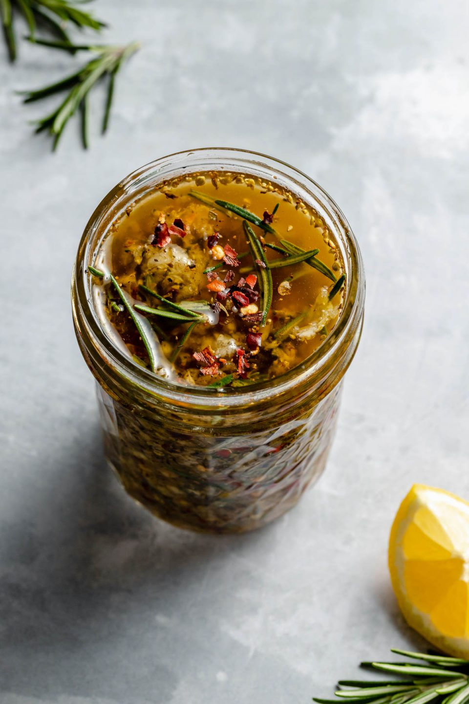 Tuscan marinade shown in a small ball jar, sitting atop a light blue surface with a lemon wedge in the foreground & fresh rosemary sprigs in the background.