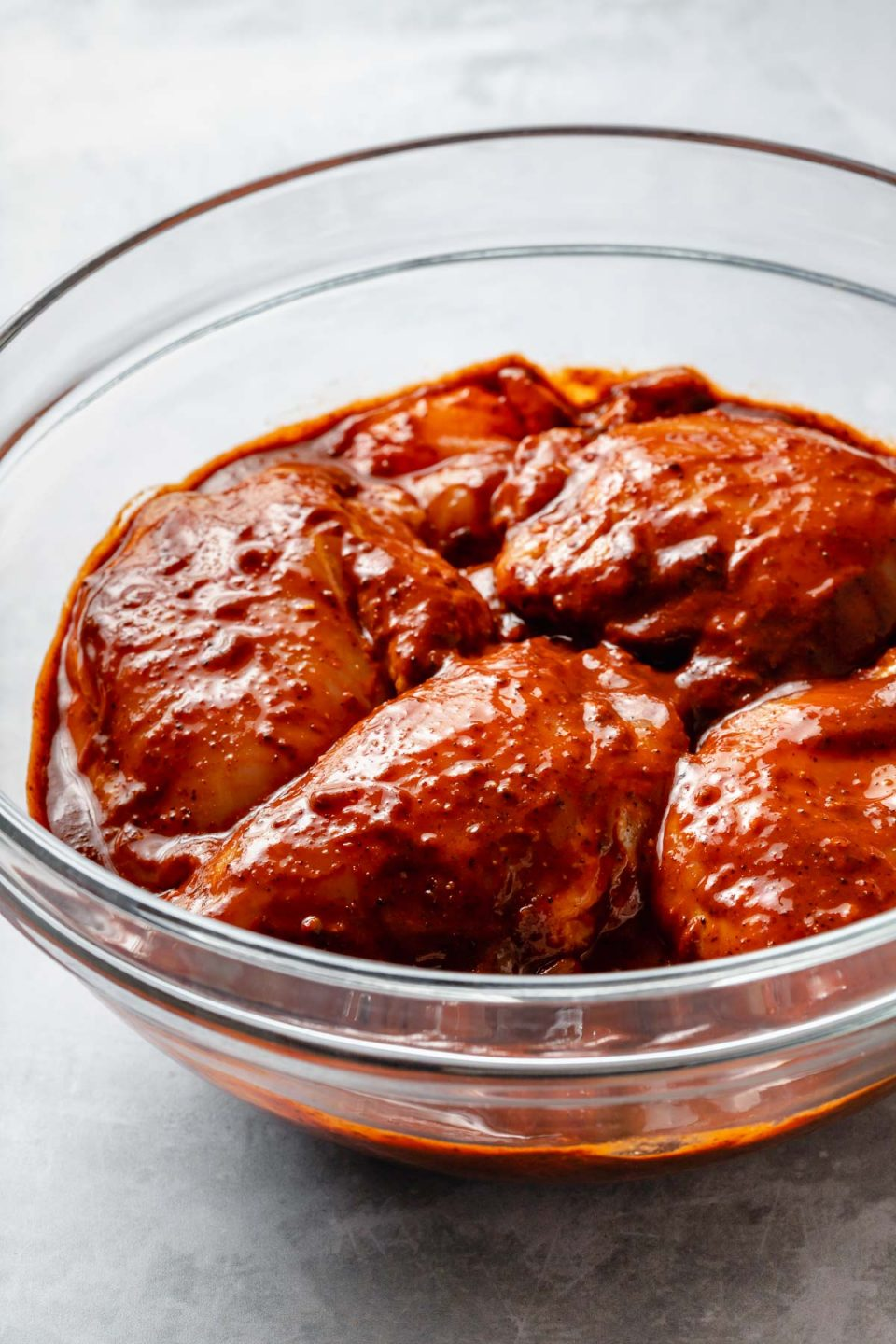 Side angle of chicken thighs in a large glass mixing bowl, marinating in Al Pastor marinade. The bowl sits atop a light blue surface.