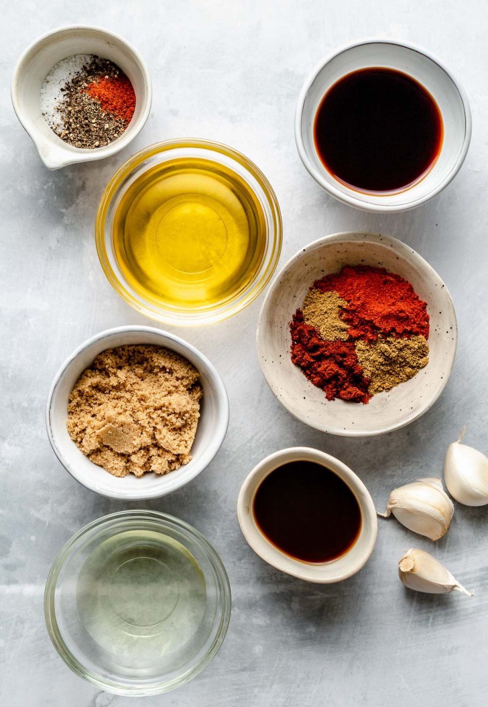 All-purpose marinade ingredients arranged on a light blue surface: olive oil, brown sugar, apple cider vinegar, low-sodium soy sauce, Worcestershire sauce, garlic, chili powder, ground cumin, smoked paprika, salt, pepper, & optional cayenne pepper.