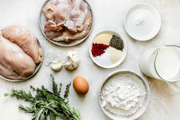 Buttermilk fried chicken ingredients arranged on a creamy white surface: boneless, skinless chicken thighs & breasts, garlic, fresh poultry herbs, egg, flour, buttermilk, spice blend & baking powder.