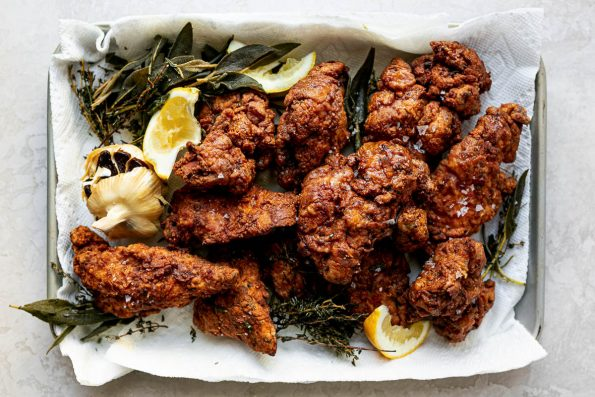 A top down shot of pieces of crispy, golden brown fried chicken, sprinkled in flaky salt, piled onto a quarter sheet pan lined with paper towels. Leftover herbs & garlic from the frying oil and lemon slices resting next to and around the pieces of chicken.