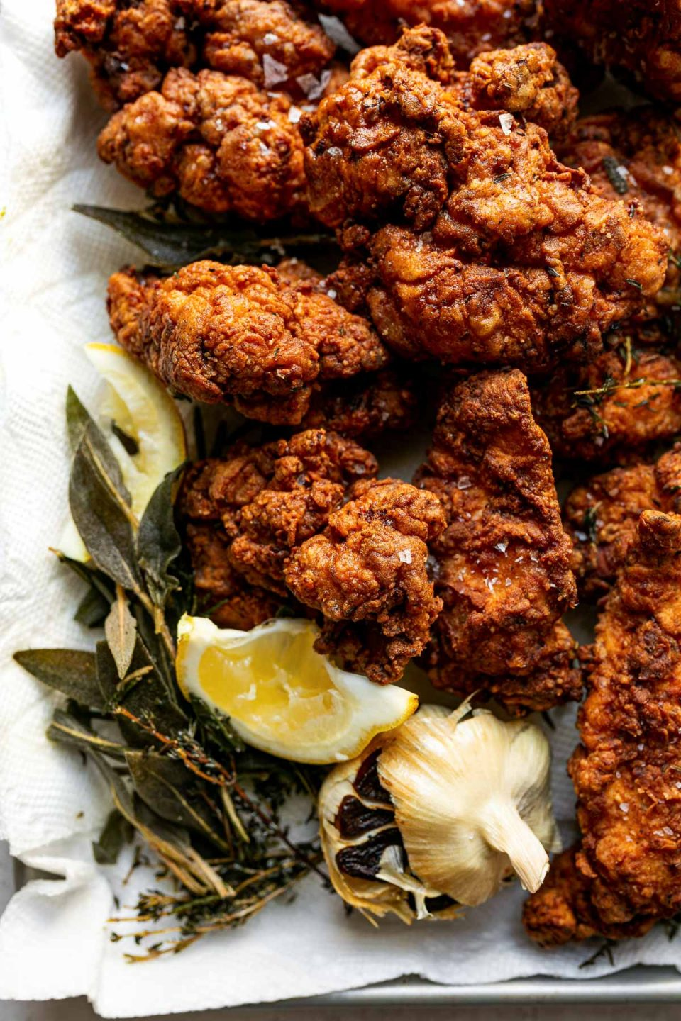A close up shot of crispy, golden brown fried chicken piled onto a quarter sheet pan lined with paper towels with leftover herbs & garlic from the frying oil and two lemon slices resting next to it.