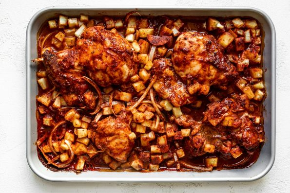 Baked al pastor chicken thighs & sliced onion on a silver quarter baking sheet with finely diced pineapple. The sheet pan sits atop a white plaster surface.