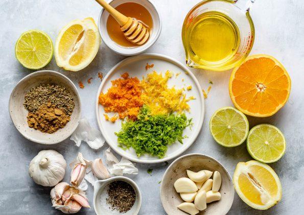 Mojo marinade ingredients arranged on a light blue surface: oranges, lemons, limes, zest of all 3, garlic, cumin, salt, pepper, honey, & olive oil.