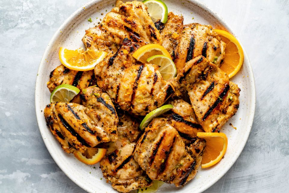 Grilled mojo chicken thighs on a speckled white plate atop a light blue surface. The chicken thighs are garnished with orange & lime wedges & zest.