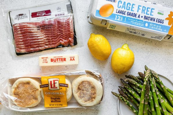 Eggs benedict ingredients from ALDI - Appleton Farms Center-Cut Bacon, L'Oven Fresh English Muffins, lemons, butter, asparagus & Gold Hen Cage-Free Brown Eggs - atop a white surface.