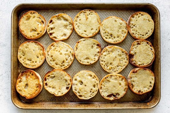 Toasted English muffins on a baking sheet atop a white surface.