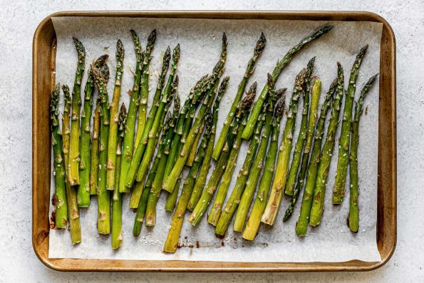 Roasted asparagus on a parchment-lined baking sheet atop a white surface.