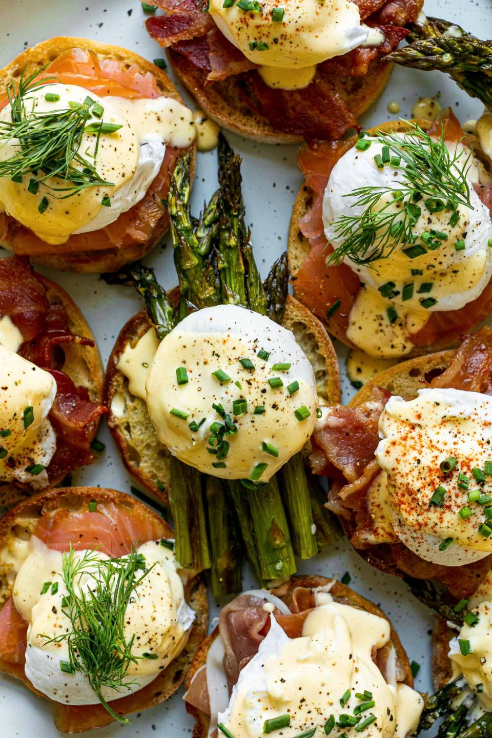 Eggs benedict variations with asparagus, bacon, prosciutto & smoked salmon atop a light blue speckled platter, atop a white surface.