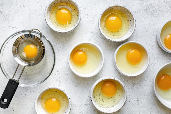 Poached eggs prep: eggs cracked into individual bowls. One egg is cracked in a small strainer to strain the whites. All of the bowls sit atop a white surface.