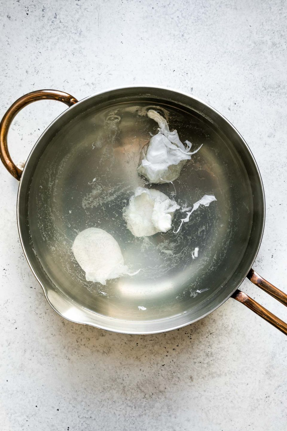 3 eggs poaching in simmering water in a saucepan, atop a white surface.