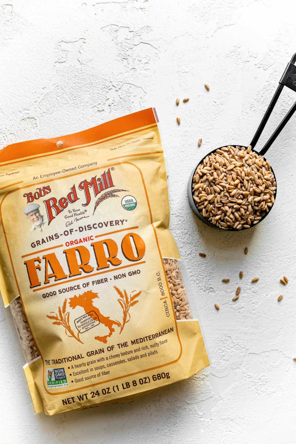 Bag of Bob's Red Mill farro on a white surface next to black measuring cup with farro in it.