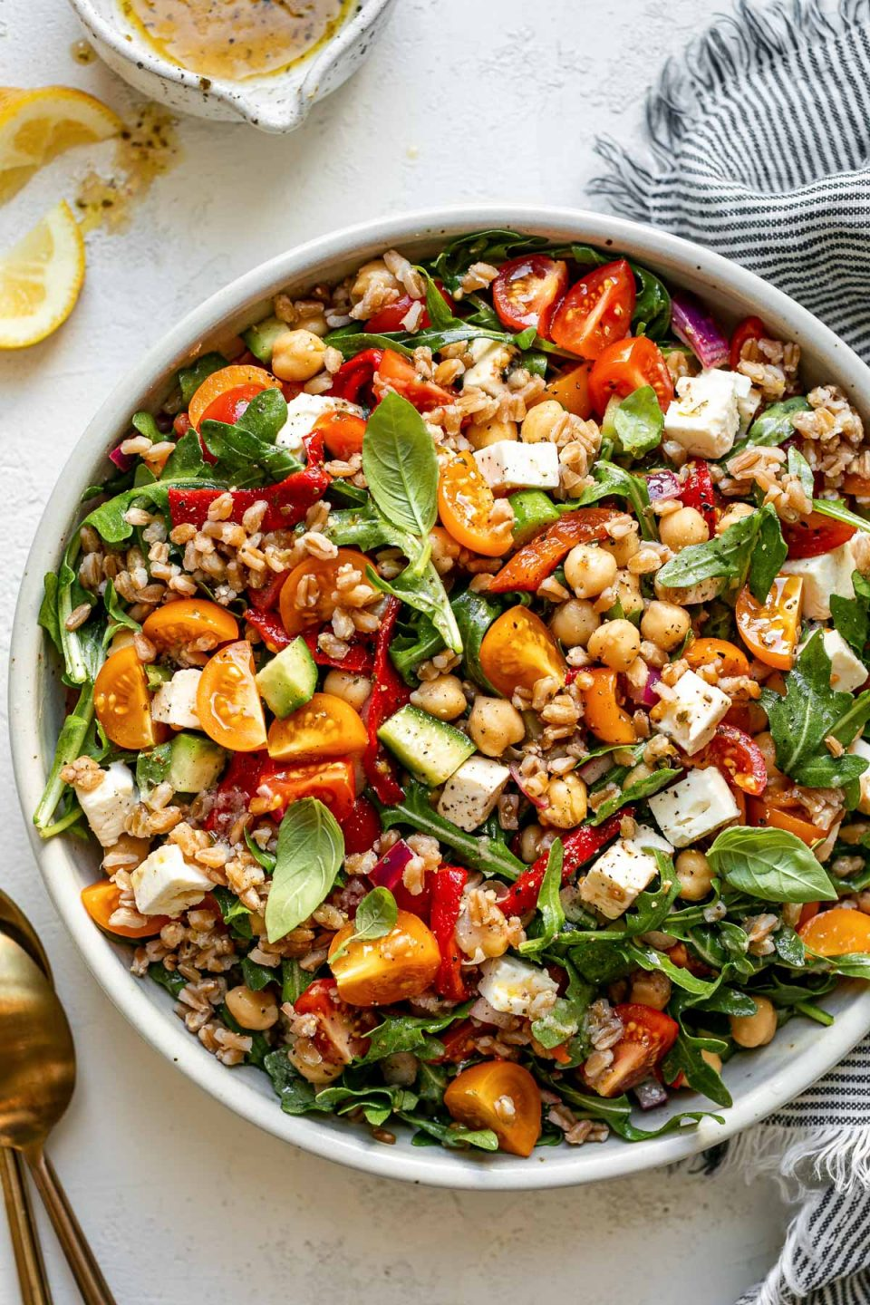 Greek farro salad in ceramic serving dish atop a white surface. The farro salad is tossed & topped with fresh basil leaves. The bowl is surrounded by a striped gray linen napkin, serving spoons, lemon wedges.