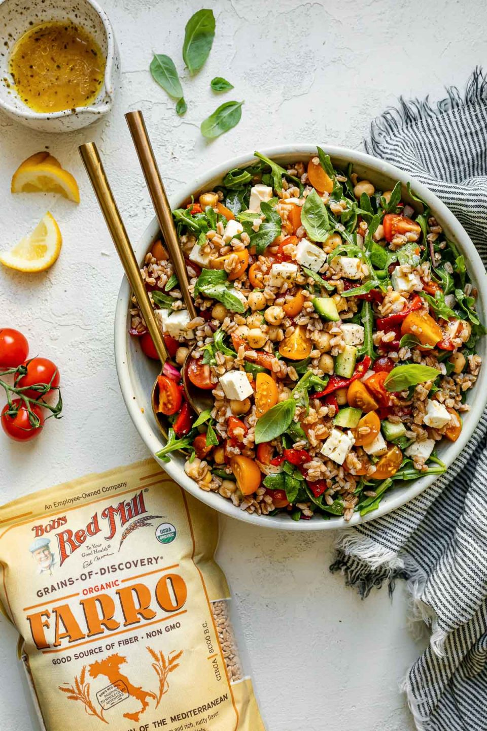 Greek farro salad in ceramic serving dish atop a white surface. The farro salad is tossed & topped with fresh basil leaves. The bowl is surrounded by a striped gray linen napkin, lemon wedges, tomatoes, & a bag of Bob's Red Mill farro.