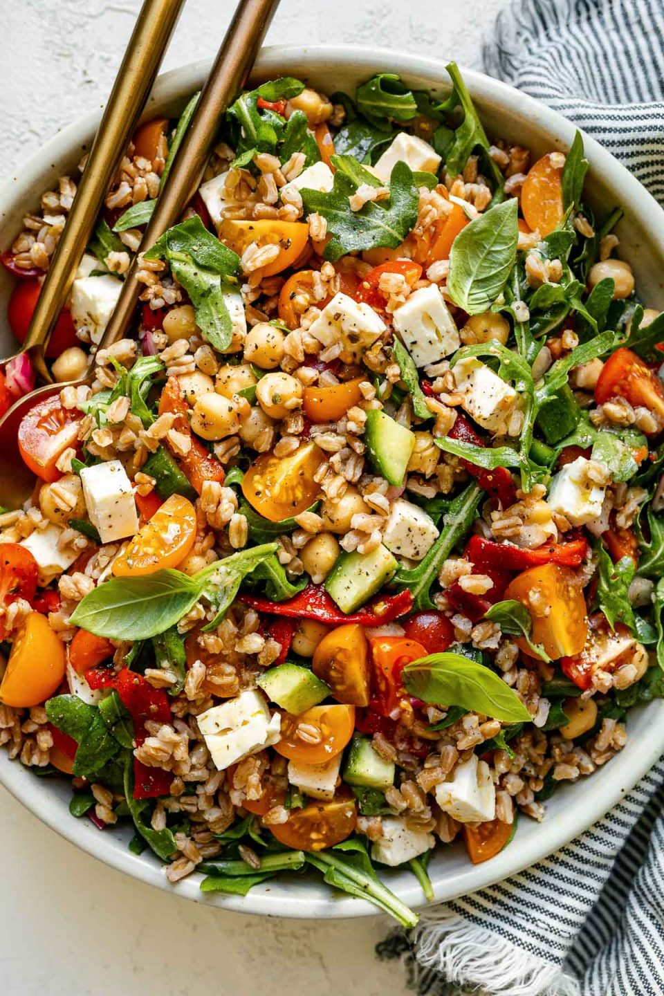 Greek farro salad in ceramic serving dish atop a white surface. The farro salad is tossed & topped with fresh basil leaves & has serving spoons nestled in it. The bowl is surrounded by a striped gray linen napkin.