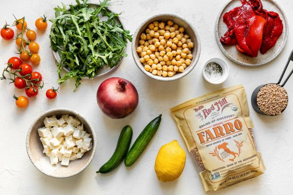 Greek farro salad ingredients arranged on a white surface: tomatoes, feta cheese, arugula, red onion, chickpeas, cucumber, lemon, Bob's Red Mill farro, & roasted red peppers.