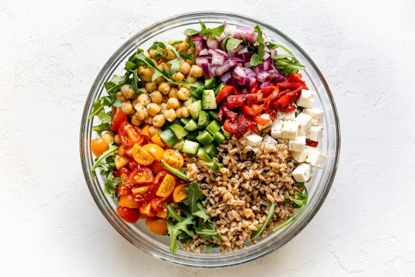 Greek farro salad in large clear glass bowl atop a white surface. The farro salad ingredients are grouped in the bowl - lemony red onions, chickpeas, cucumber, tomatoes, farro, feta, etc.