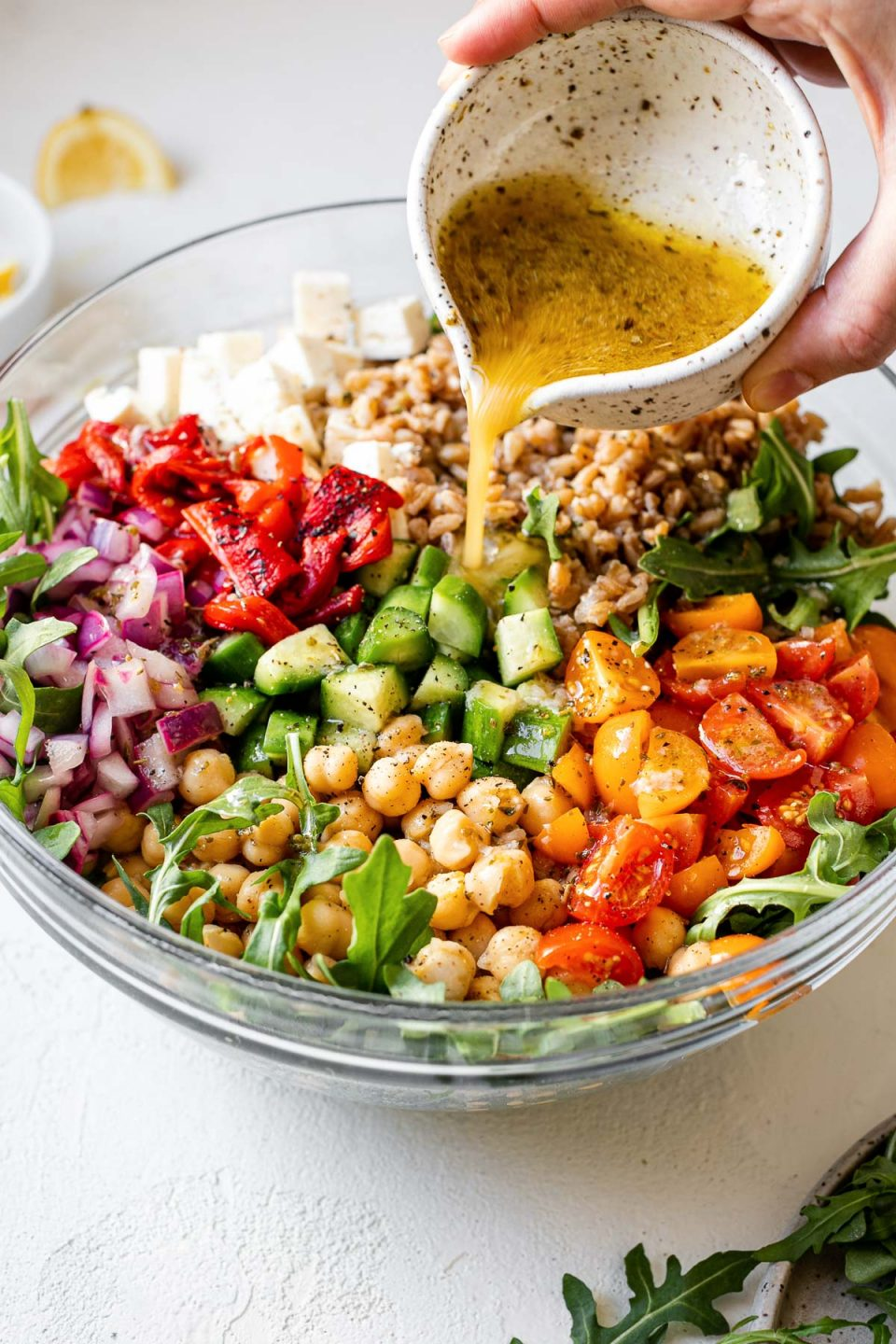 A woman's hand pours Greek dressing from bowl into Greek farro salad.