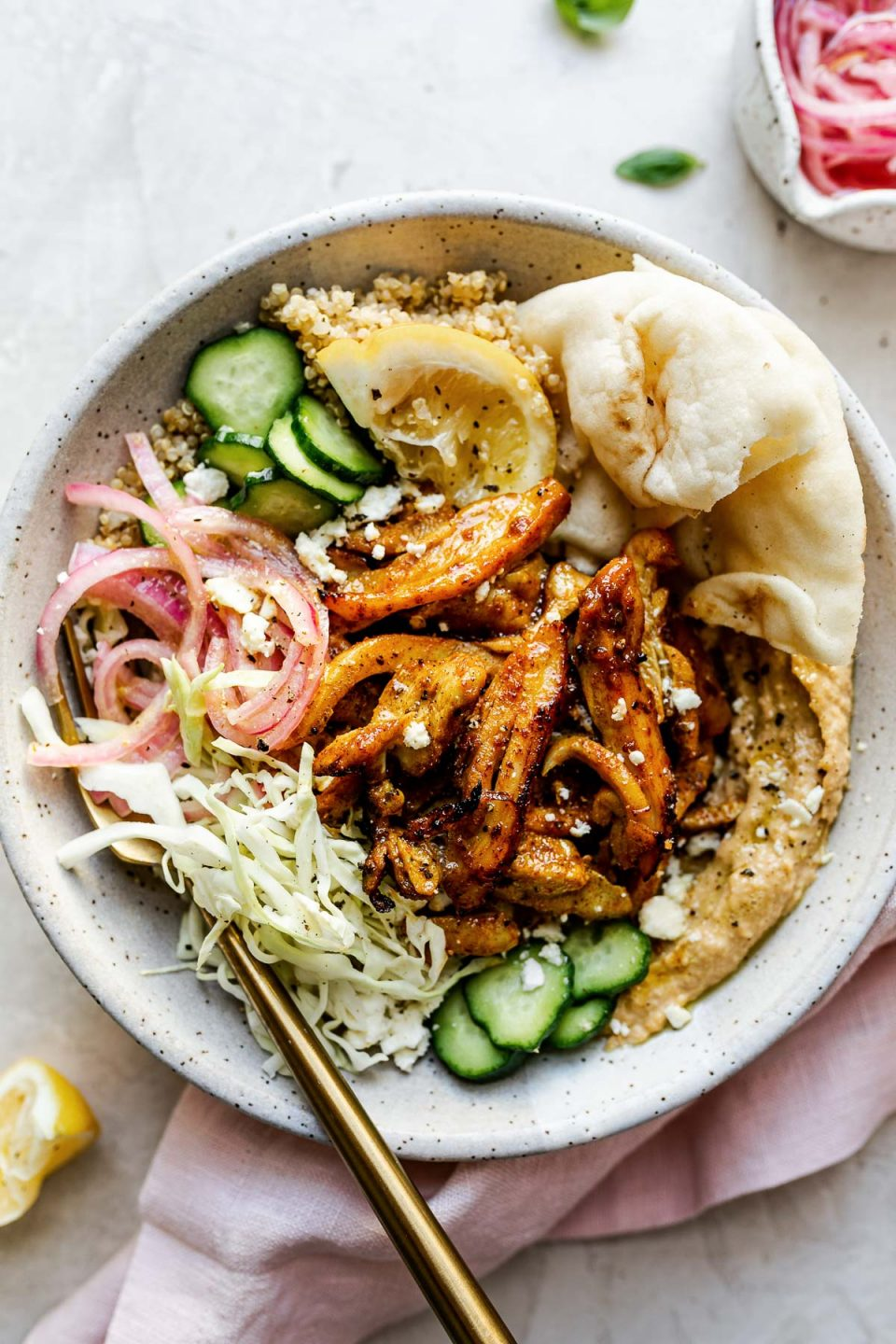 Chicken Shawarma Hummus Bowl with quinoa, cucumbers, pickled red onion, shredded cabbage, & naan bread shown in a speckled gray ceramic bowl. The bowl sits atop a creamy cement surface, surrounded by lemon wedges, fresh basil leaves, a small bowl of pickled red onions, & a pink linen napkin.