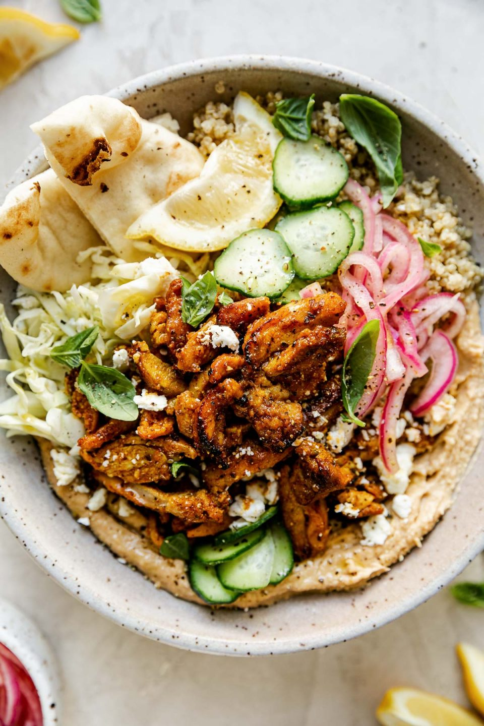Chicken Shawarma Hummus Bowl with quinoa, cucumbers, pickled red onion, shredded cabbage, & naan bread shown in a speckled gray ceramic bowl. The bowl sits atop a creamy cement surface, surrounded by lemon wedges, fresh basil leaves & a small bowl of pickled red onions.