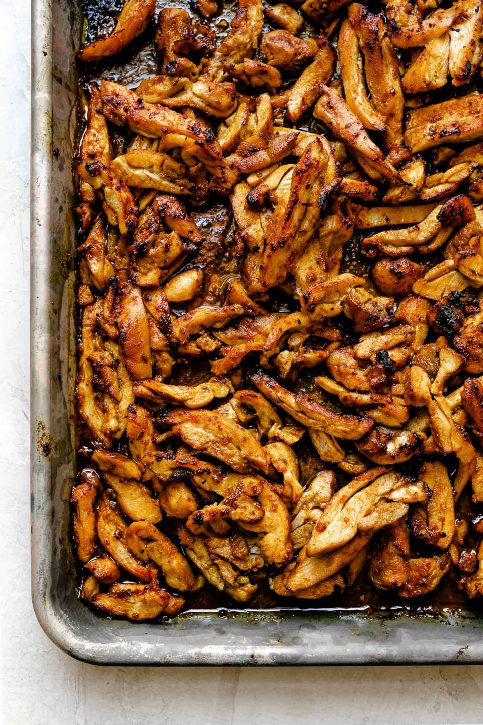 Thinly sliced broiled chicken shawarma on a small baking sheet atop a creamy cement surface.