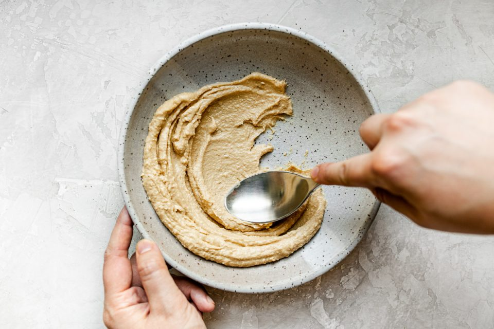 A woman's hands spreading hummus on the bottom of a speckled gray ceramic bowl with a large spoon. The bowl sits atop a creamy cement surface.