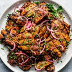 Grilled Shawarma marinated chicken thighs shown on a white speckled plate atop a light blue surface. The chicken is garnished with fresh herbs & ribbons of pickled red onion.