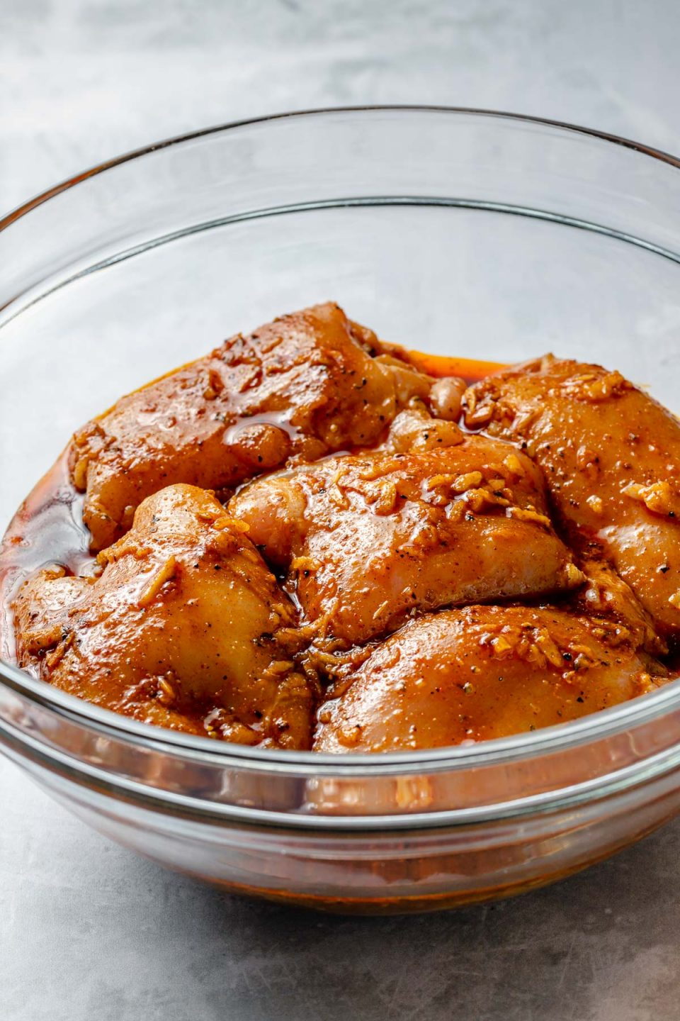 Side angle of chicken thighs in a large glass mixing bowl, marinating in Shawarma marinade. The bowl sits atop a light blue surface.