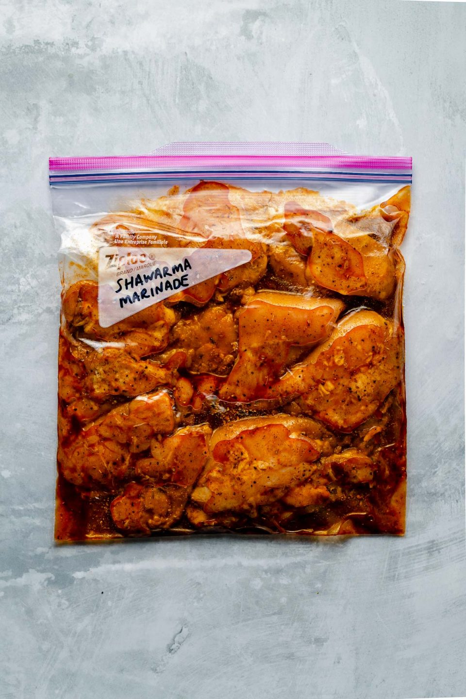 """Chicken thighs in a Ziploc bag, marinating in Shawarma marinade. The bag sits atop a light blue surface. """"Shawarma Marinade"""" is penned in the bag's memo area."""