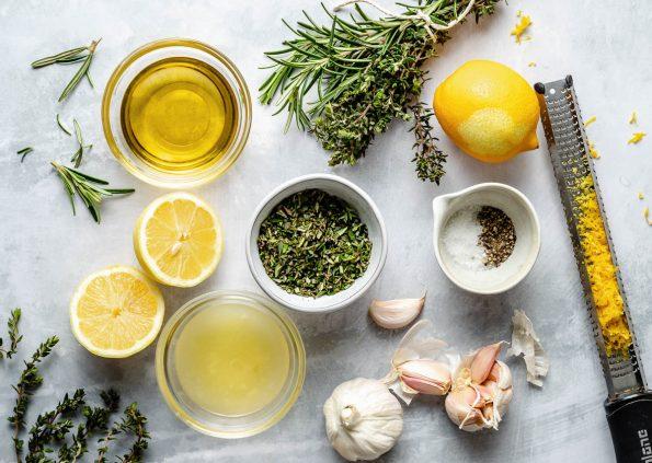Lemon herb marinade ingredients arranged on a light blue surface: lemon juice, lemon zest featured on a microplane, garlic, olive oil, fresh herbs including rosemary, thyme, & oregano, salt, & pepper.