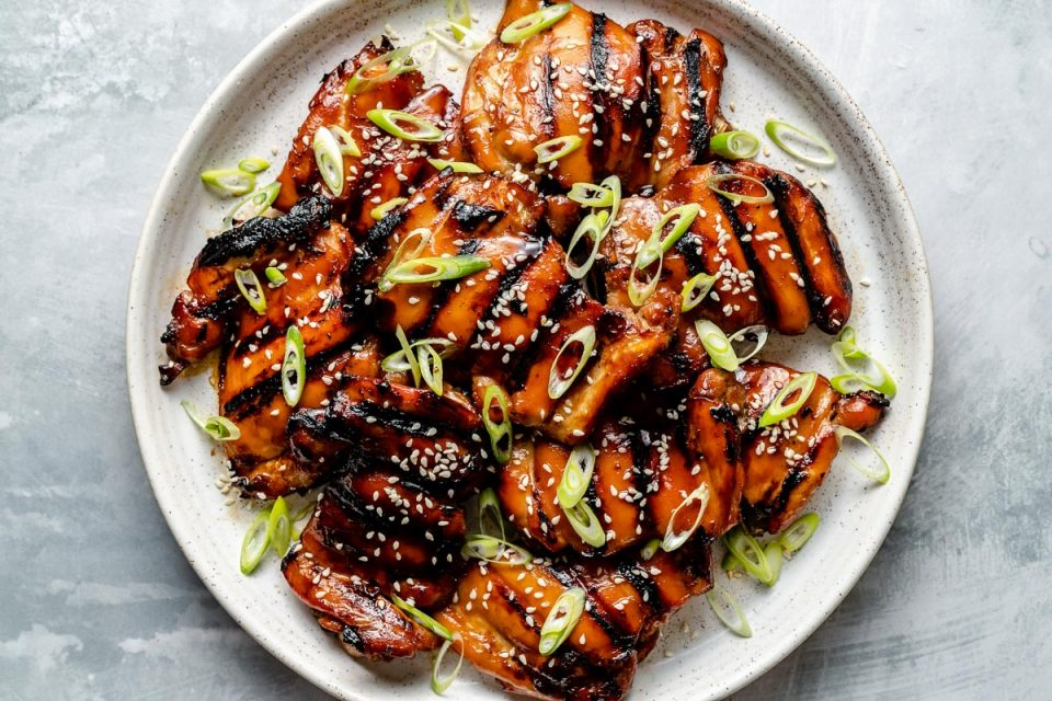 Grilled Teriyaki chicken thighs shown on a white speckled plate atop a light blue surface. The chicken is garnished with sliced green onion & sesame seeds.