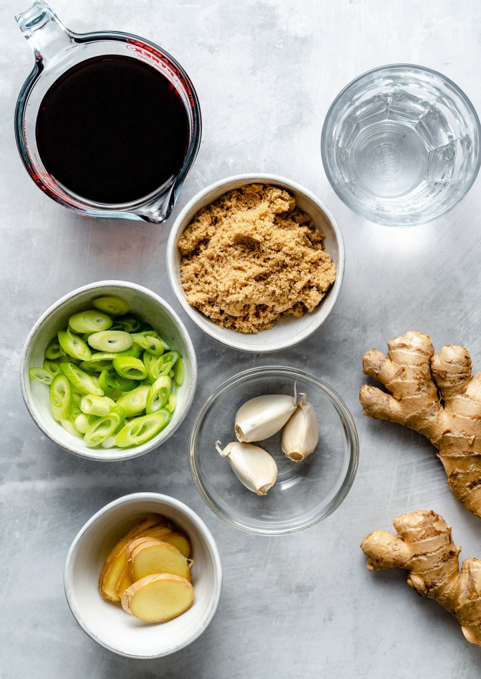 Teriyaki marinade ingredients arranged on a light blue surface: soy sauce, water, brown sugar, garlic, green onions, & fresh ginger.