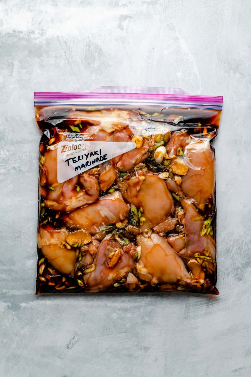 """Chicken thighs in a Ziploc bag, marinating in Teriyaki marinade. The bag sits atop a light blue surface. """"Teriyaki Marinade"""" is penned in the bag's memo area."""