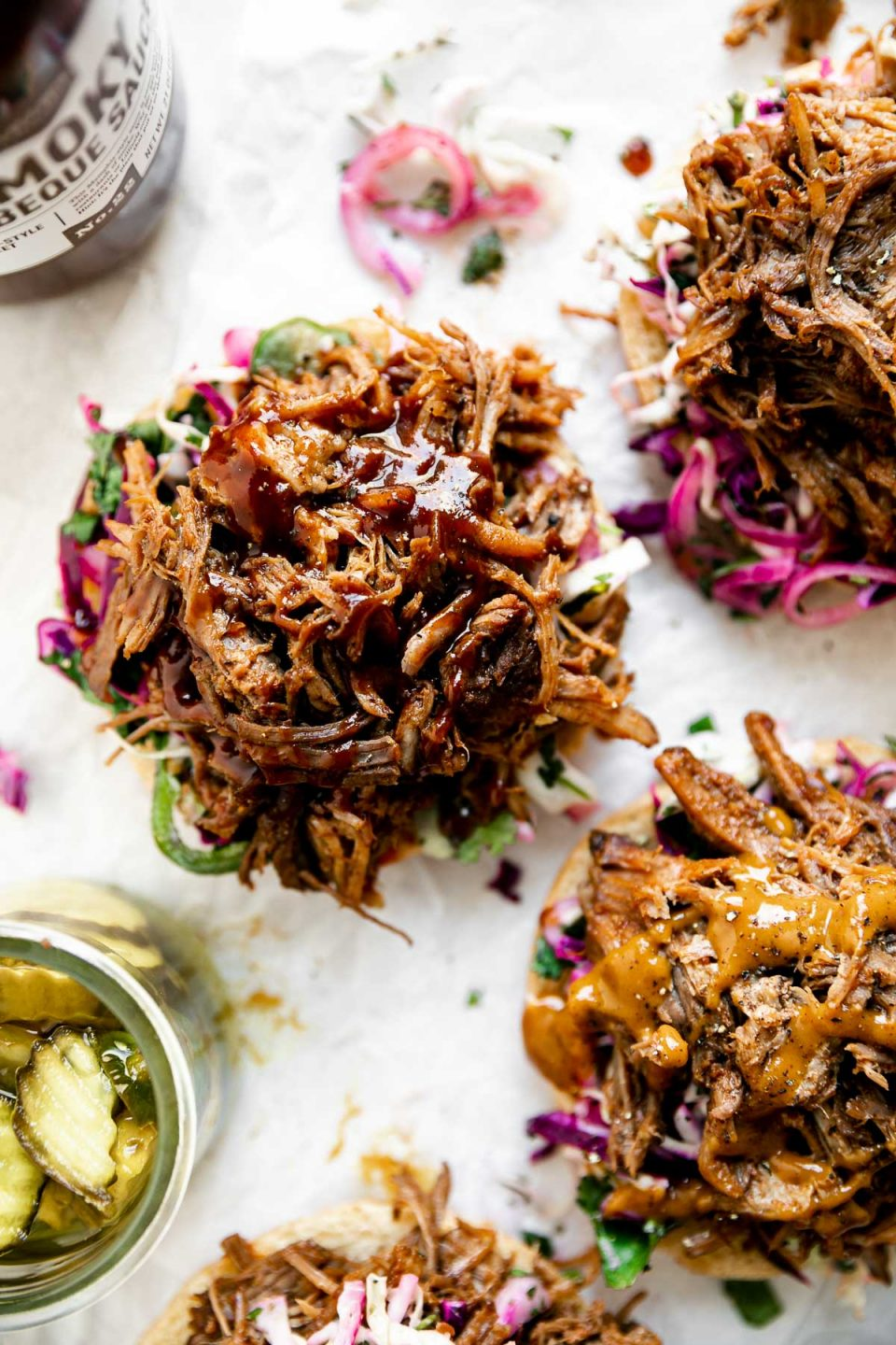 Easy pulled pork shown on 4 open face sandwiches. The pork sits atop buns & slaw on a white surface, alongside a jar of pickles & BBQ sauce.