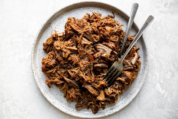 How to make bbq pulled pork, step 3: shredded pork shown on a speckled ceramic plate, with 2 forks. The plate sits atop a creamy cement surface.