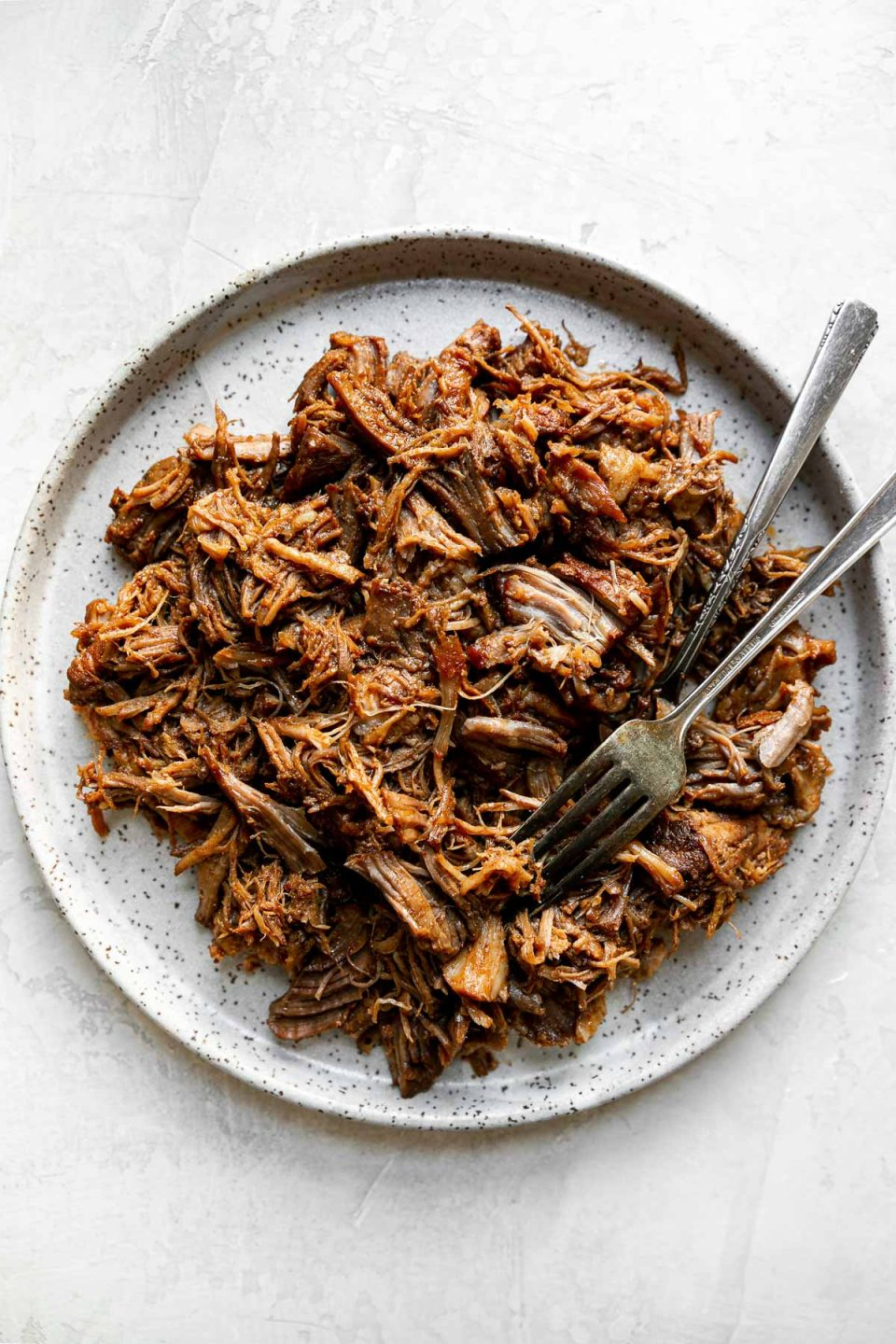 Shredded pork shown on a speckled ceramic plate, with 2 forks. The plate sits atop a creamy cement surface.