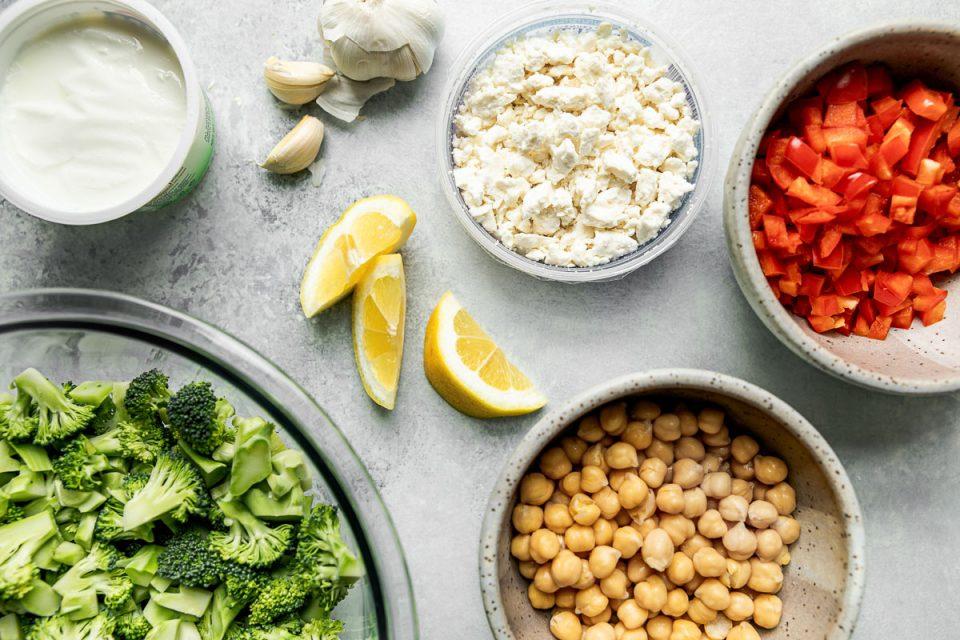 Healthy broccoli salad ingredients arranged on a light gray surface – broccoli, Greek yogurt, garlic, feta, chickpeas, lemon wedges & diced red bell pepper.