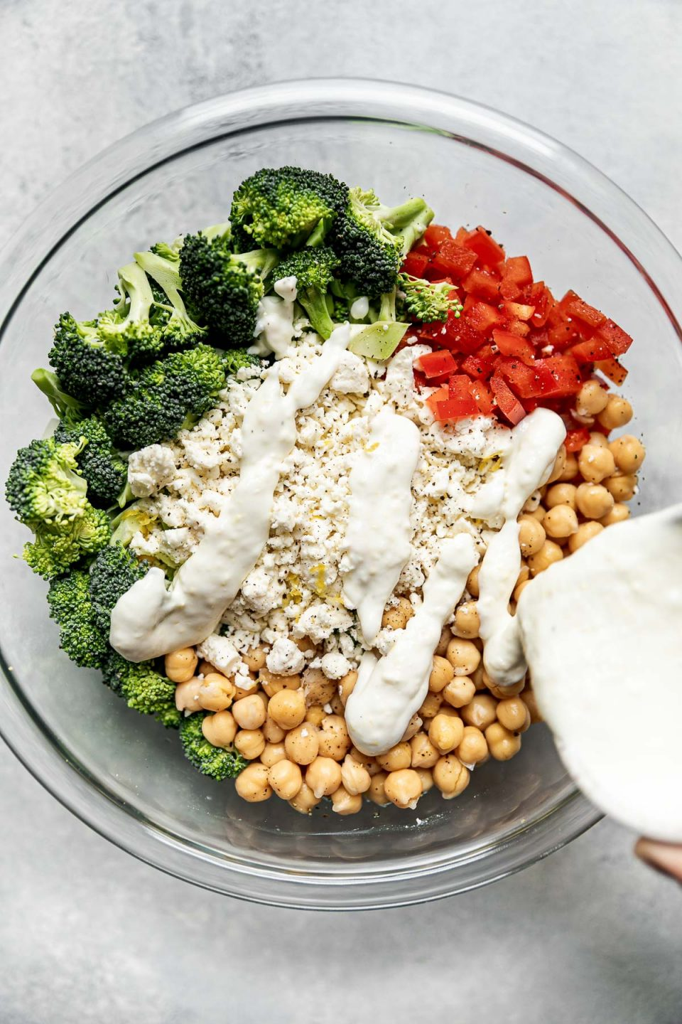 Pouring Greek yogurt dressing over broccoli salad ingredients (broccoli florets, chickpeas, diced bell pepper & feta) shown in a large glass mixing bowl atop a light gray surface.