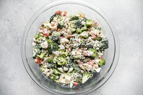 Dressed healthy broccoli salad shown in a large glass mixing bowl atop a light gray surface.