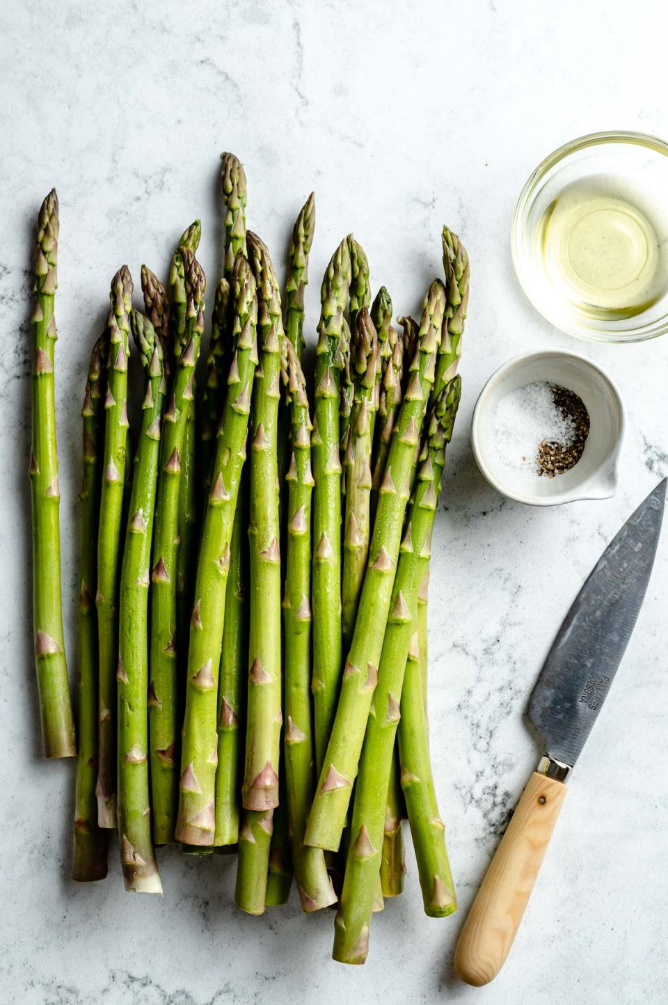 Grilled asparagus ingredients arranged on a white & grey marble surface - asparagus, avocado oil, kosher salt, & ground black pepper. A pairing knife rests on the surface next to the ingredients.