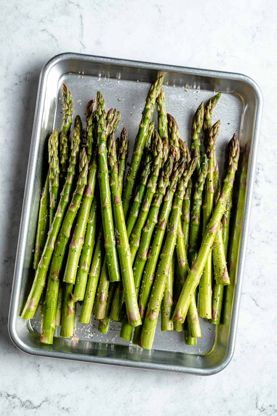 Fresh & raw asparagus spears seasoned with avocado oil, kosher salt, & ground black pepper arranged on an aluminum baking sheet. The baking sheet sits on top of a white & gray marble surface.