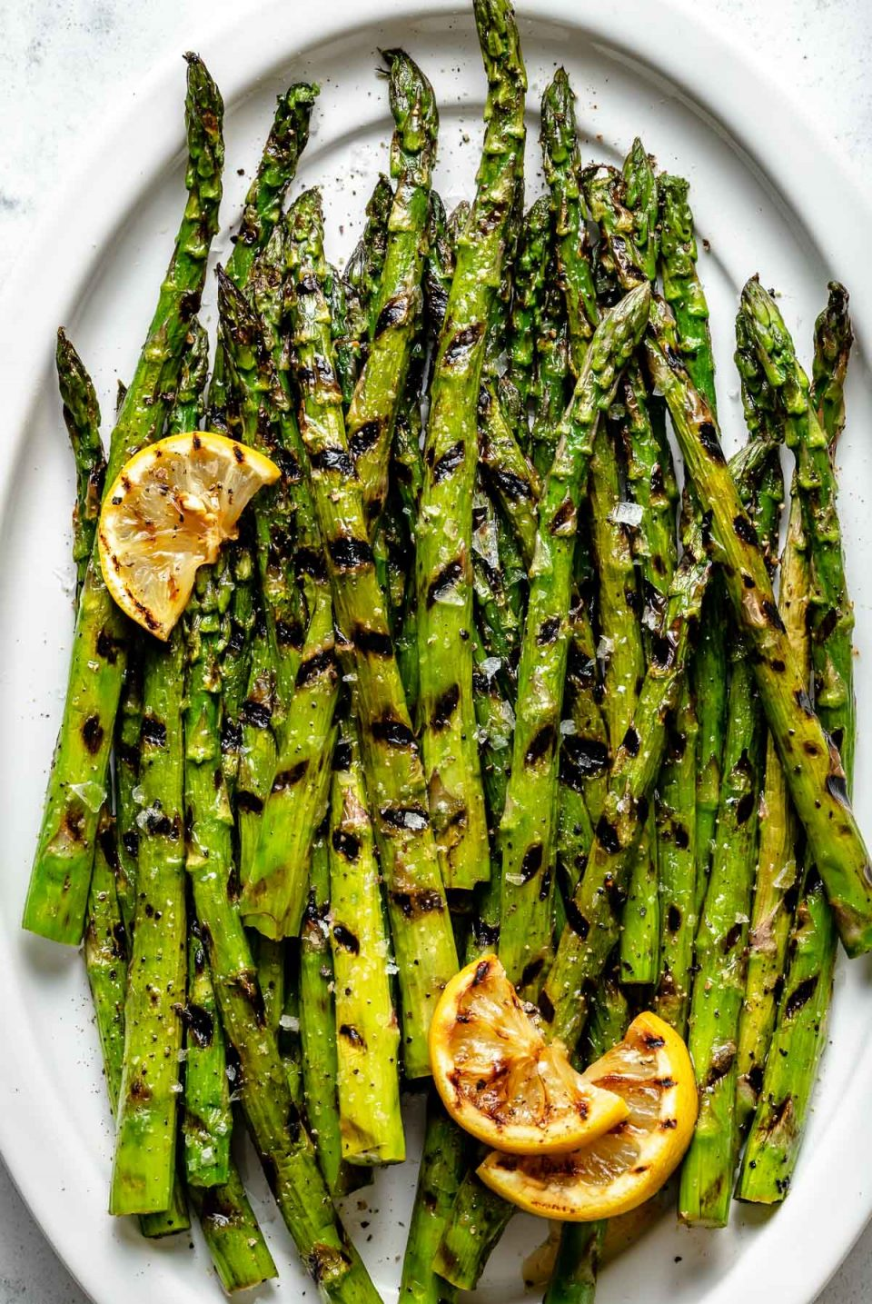Close up of grilled asparagus spears with char marks arranged on a white ceramic platter. The grilled asparagus is garnished with kosher salt, ground black pepper, & grilled lemons. The platter sits on top of a white & gray marble surface.