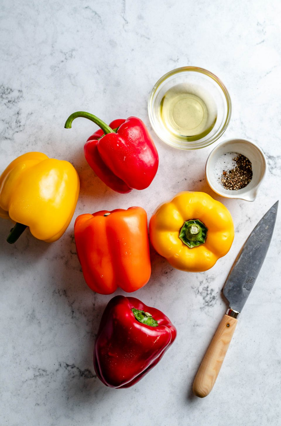 Grilled bell pepper ingredients arranged on a white & grey marble surface - yellow, orange, & red bell peppers, avocado oil, kosher salt, & ground black pepper. A pairing knife rests on the surface next to the ingredients.